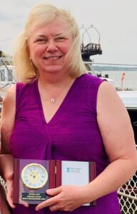 Betty Rockendorf holding her WHIMA educator award